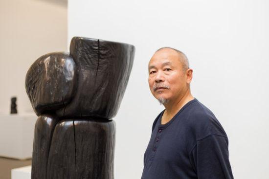 王克平和他的木雕作品。