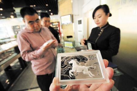 马年金银纪念币陆续面世,图为收藏爱好者在咨询。IC图