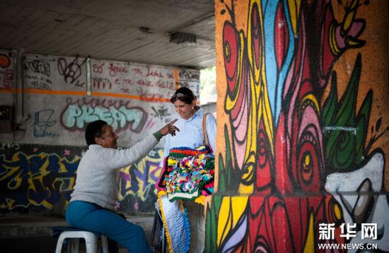2011年8月26日里约热内卢:涂鸦之城8月25日,在巴西最大城市里约热内卢,一名妇女在一座画有涂鸦的立交桥下贩卖商品。