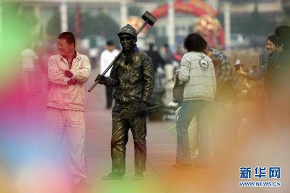 """10月7日,慕丰喜装扮成的""""雕塑""""成为烟台市滨海的一道风景。新华社发(申吉忠 摄)"""