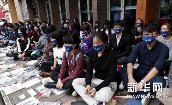 """11月23日,参与者戴着""""今天不说话""""的口罩静坐在街头。新华网图片 凡军 摄"""