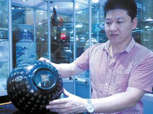 周勇锋向记者展示他收藏的碧玉碗。 肖亮 摄