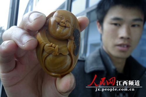 """宜豐縣黃崗山墾殖場一青年展示他請人雕刻的黃蠟石雕""""笑面佛""""。"""