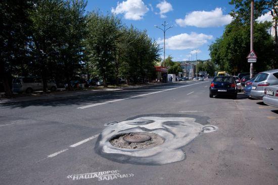 俄罗斯叶卡捷琳堡,艺术家涂鸦恶搞地方政客,讽刺城市道路坑洼现状。
