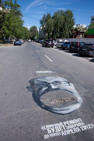 """艺术家涂鸦恶搞地方政客,讽刺城市道路坑洼现状。左边的文字写到""""所有的街道将被改建为适当的状态。"""""""