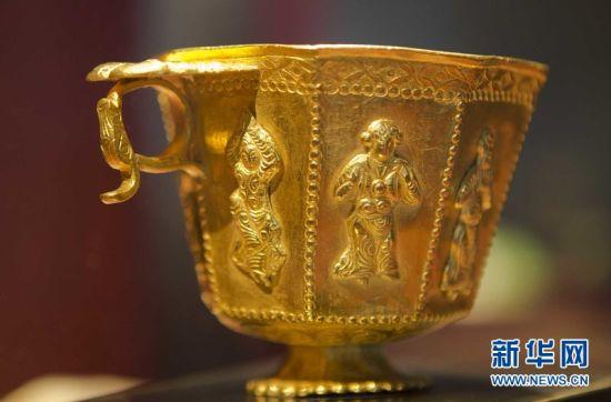 """從""""黑石號""""沉船上打撈起的八棱胡人伎樂金杯——杯麵上的舞伎長發飛揚,有胡人之貌。這是在中國境外發現的最重要的唐代金器之一。新華網 鄒崢攝"""