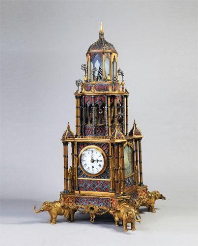"""18世紀鎏金塔式鐘通高65厘米,寬32厘米,厚30厘米。此鐘為英國製造,錶盤上部寫有花體""""Geo.Pyke"""",下部為花體""""London""""(倫敦)字樣。"""
