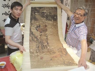 杨老父子展示待修复的《松鸡图》。 万凌云 摄