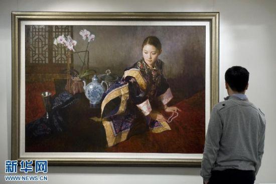 苏富比工作人员观看画家陈衍宁的作品《夜深沉》。