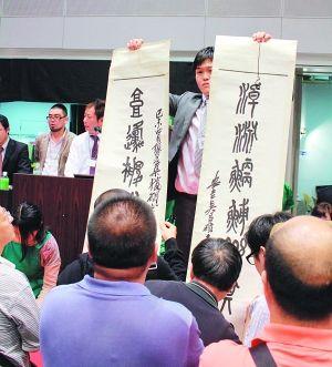 名古屋中日拍卖会的工作人员正站在桌上,打开吴昌硕款对联拍品供看官急扫,约5秒钟后开始竞价。 陆斯嘉 图