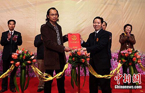 世界纪录协会认证官习操先生(右)为这幅长达365米的油画长卷颁发了世界纪录证书。
