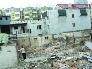 一名女子站在北总布胡同24号的废墟上。
