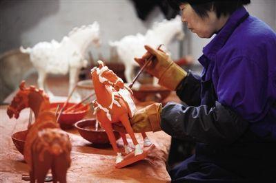 """3月30日,洛阳南石山村一家文物复制品工厂内,工作人员在给""""马""""上釉彩。A10-11版摄影/山石"""