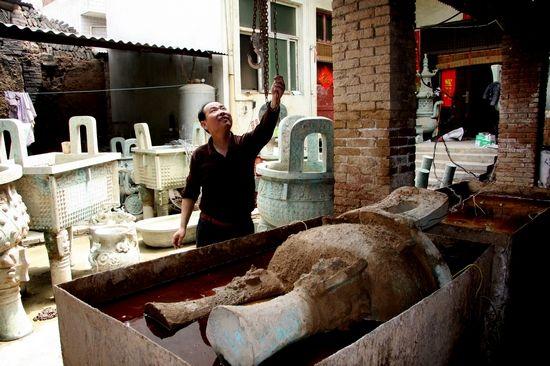 河南省洛阳烟涧村的青铜器高仿作坊中,一件半成品被浸泡进电解水中,进入做旧工序
