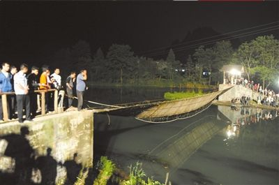 昨晚,凤凰县通往桃花岛的吊桥桥面已倾斜。中新社发