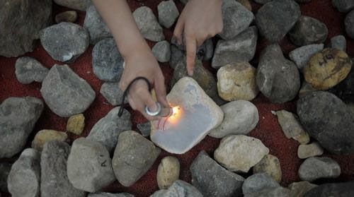 一塊翡翠原石在強光手電照射下晶瑩剔透,然而,誰都不敢保證它內部的成色究竟如何本組圖片記者劉陽攝