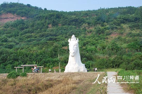"""""""天马""""雕塑前面杂草丛生,未见绿化带和标识标牌。(记者郭洪兴 摄)"""