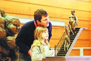 """一对法国父女在罗浮宫卡鲁斯厅""""欢乐岭南""""大展上欣赏胖女雕塑"""