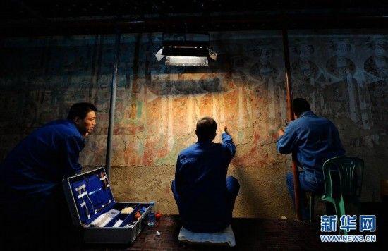 9月3日,三名技术人员在莫高窟98窟内对病害壁画进行修复。新华社记者 陈斌 摄
