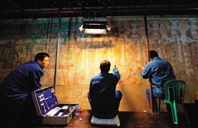 9月3日,三名技术人员在莫高窟98窟内对病害壁画进行修复。