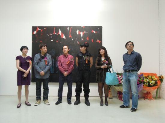 展览现场画家(中)和嘉宾合影。