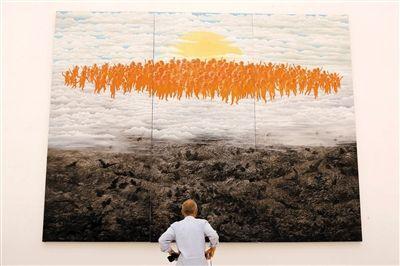 昨日,2012年中国艺术品产业博览会亮相宋庄。一位观众在观看方力钧的巨幅油画新作《2011秋》。 新京报记者 郭延冰 摄