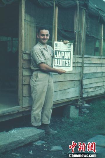 驻芷江美军通讯兵约瑟夫的战友展示日本无条件投降的外文报纸。 当年驻芷江美军约瑟夫供图。 摄